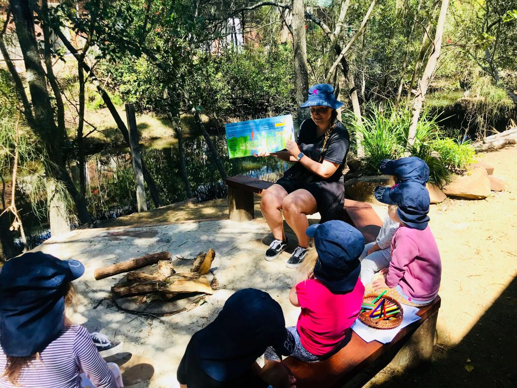 Bush Kindy - A Group Of Children From An Early Learning Centre Around A Camp Fire While The Early Childhood Educator Reads A Story