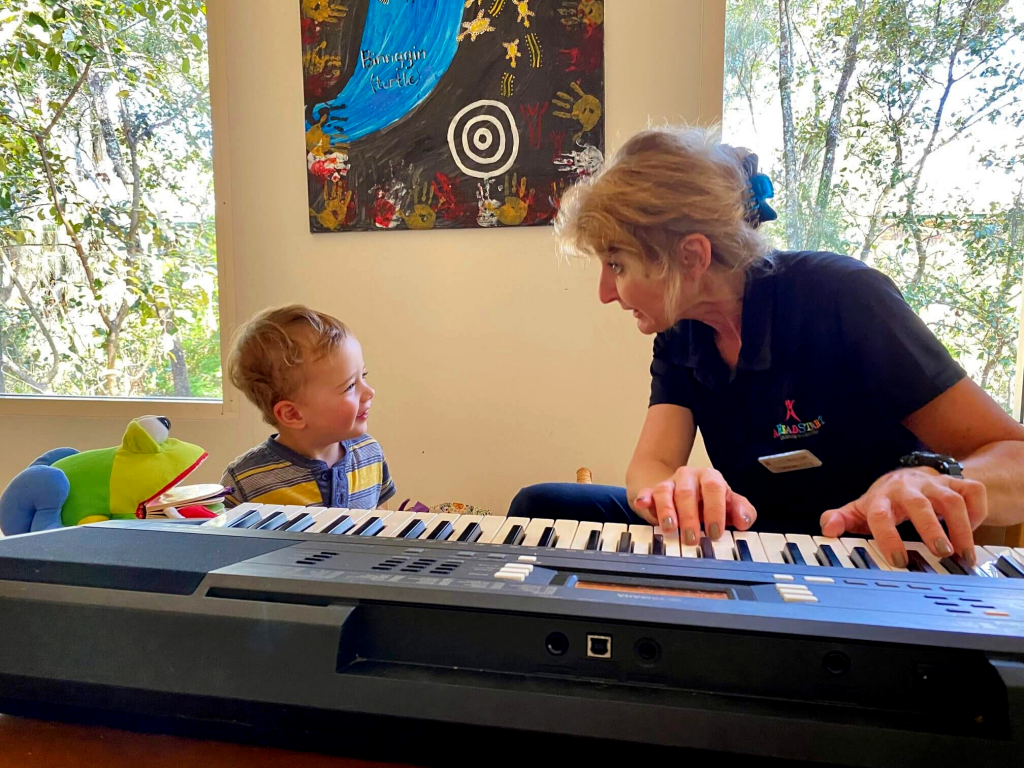 Early Childhood Educator Plays Music On Keyboard For Child